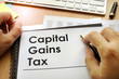 Hands holding documents with title capital gains tax CGT. - 159730502