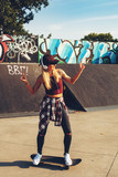 Young woman on a skateboard and listening to music in skate park