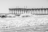 Pier in rough seas in black and white