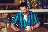 happy man with smartphone and coffee at restaurant