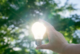Woman hands holding light bulb with solar energy or thermal energy concept. - 159753718