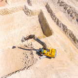 Aerial view of a excavator in open cast mine or on construction site. Heavy industry from above. Industrial background from drone.  - 159757354