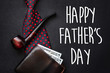happy father's day text sign. fathers day greeting card.  flat lay. bow tie leather wallet with money wooden tobacco pipe on black background with space for text, top view.