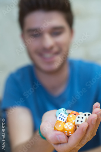 young man holding dices плакат