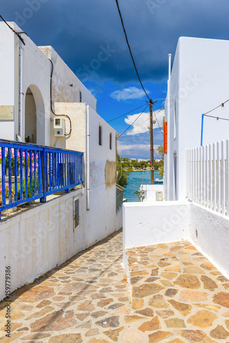 Narrow street and white houses and blue sea in background in Pollonia, Milos Island. Cyclades. Greece.