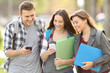 Three students checking smart phones
