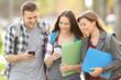 Three students checking smart phones