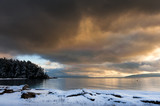 A Winter Storm in the San Juan Islands. Snow covers the coastline on Lummi Island in the San Juan Island archipelago. Dramatic clouds cover the sky all the way to the horizon.