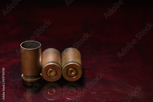 Poster Empty casings from bullets of small caliber gun on a background of red glass