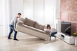 Couple Placing Sofa At Their New Home