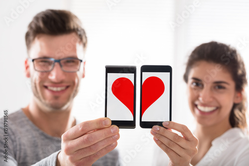 Couple Showing Heart Shape On Cell Phone