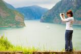 Female tourist taking photo at norwegian fjord