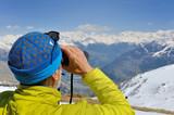 homme observant la montagne aux jumelles
