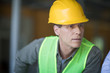 Close-up portrait of professional middle aged engineer in hard hat looking away