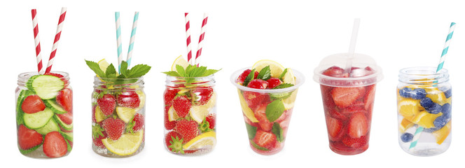 Drinks from strawberries, blueberries, orange, cucumber. Collage of lemonades isolated on white background. Set of different refreshing drink with striped straw. Drinks in a glass jar.