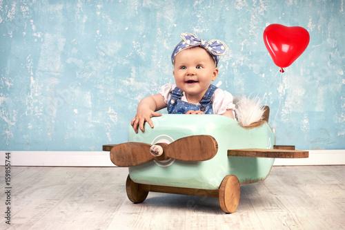 kleines Mädchen im Holzflieger mit Ballon