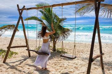 Attraktive Frau in weißem Kleid auf einer Schaukel am Strand in der Karibik