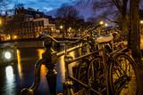 Fahrräder an der Gracht in Amsterdam bei Nacht