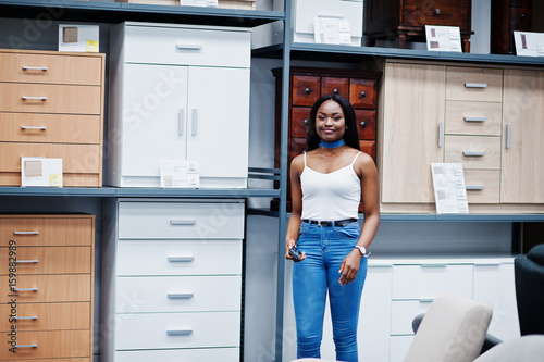 Portrait of a perfect african american woman using her smartphone in the shop Poster