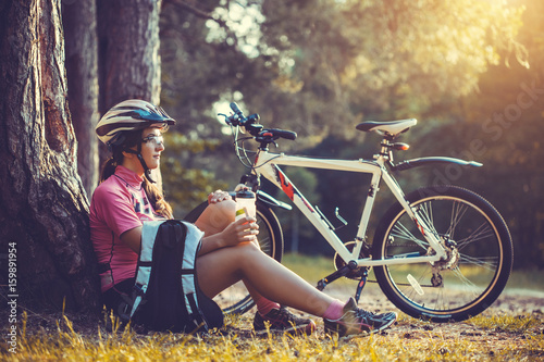 Cyclist resting under a tree and drinking water - 159891954