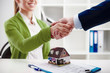 Woman agent shaking hands with new apartment owner over house model at the desk.