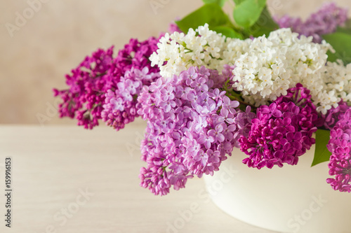 Beautiful, purple, pink and white lilac flowers in the big vase on the table. Cozy atmosphere with fresh, fragrant flowers.