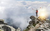 Tourist on the top of a mountain peak. Freedom - the concept.