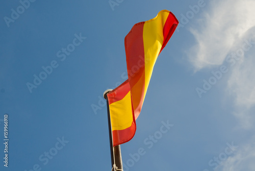 A vibrant red and yellow Spanish flag, blowing in the wind isolated on a vibrant blue sunny sky backdrop.