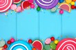 Double border of assorted colorful candies against a blue wood background