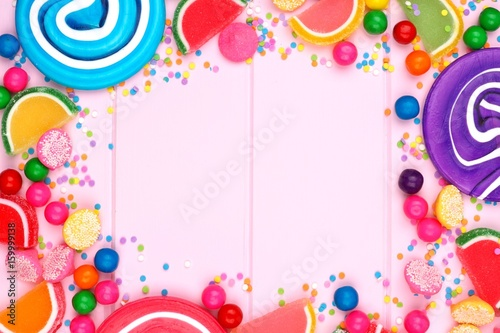 Frame of assorted colorful candies against a pink wood background - 159999138