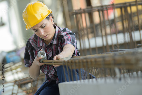 woman measuring a wooden board with a tape measure - 160006949