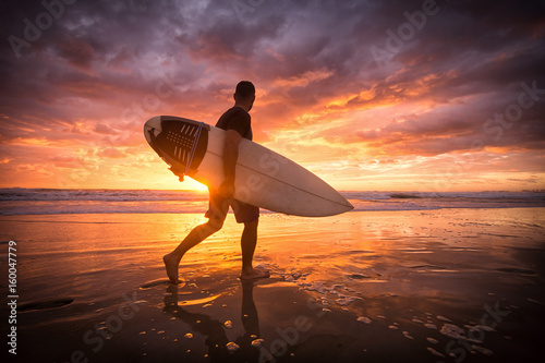 Surfer running on the beach ar sunset or sunrise