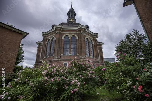 Kirchgarten mit blühenden Rosen vor einer Kirche in Hamburg