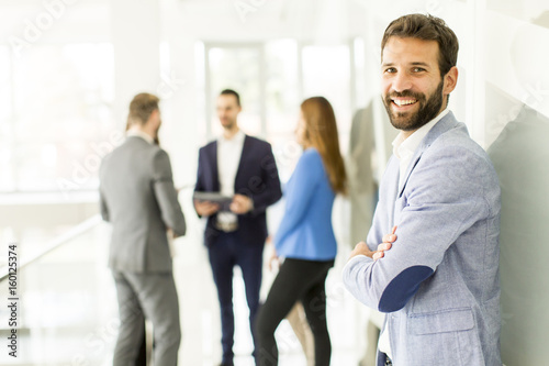 Portrait of handsome young businessman standing