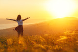 Happy woman standing with her back on sunset in nature iwith open hands.