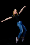 Cheerful young blonde dancing on a black background