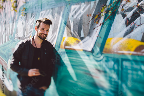Man with leather jacket leaning on graffiti wall