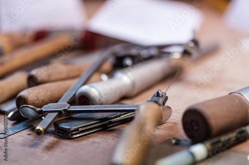Diverse Werkzeuge und eine Säge auf einem Schreibtisch in einem Juweliersbetrieb © fotografirma