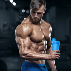 Muscular man in gym with shaker, shaped abdominal. Strong male torso abs, working out