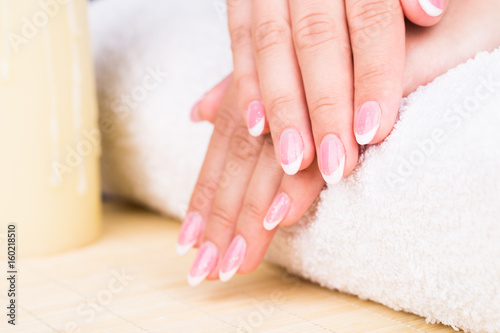 Manicure - Beauty treatment photo of nice manicured woman fingernails. Very nice feminine French manicure with shimmery top coat.  © tamara83