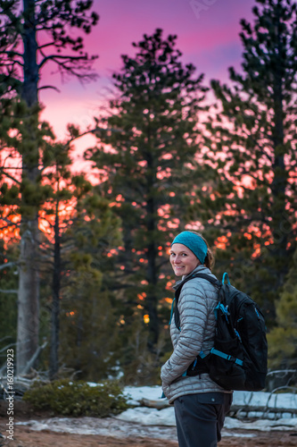 Plagát Woman Looks Back at Camera with Bright Sunset