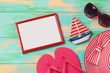 Summer vacation background with photo frame, flip flops, sunglasses and hat on wooden board. View from above