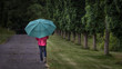 Woman under a green umbrella walking down a garden path on a rainy day at the New Jersey Botanical Gardens in Ringwood, NJ
