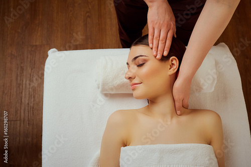Massage the head of neck to a young woman in massage room.