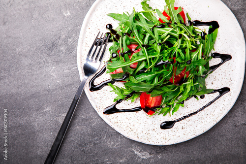 Salad with arugula , Fresh Cherry Tomatoes with Balsamic dressing and Olive oil.Food or Healthy diet concept.Super Food.Vegetarian.Top View.Copy space for Text.