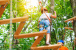 A child accompanied by an adult moves on ropes course