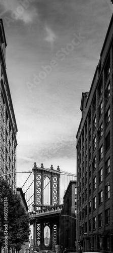 Manhattan Bridge seen through buildings, black and white, New York City, USA.