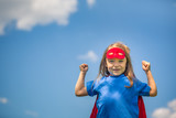 Funny little girl playing power super hero over blue sky background. Superhero concept. - 160394922