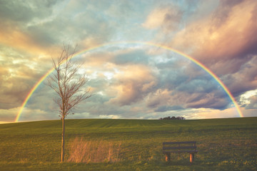 Spring rain and rainbow over the field.Vintage color tone