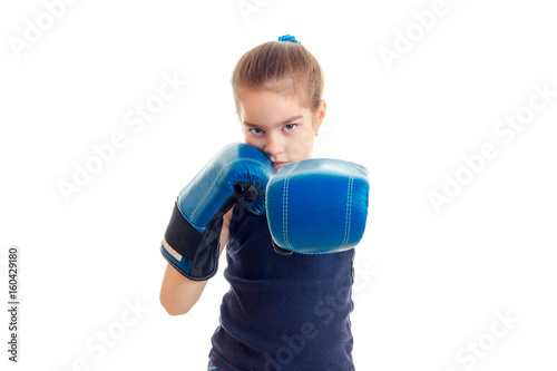 little serious girl with boxing gloves stands in front of the camera and pulls the hands